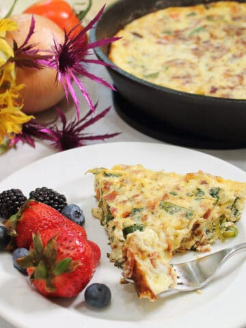 Serving on white plate with bite on fork and fruit on the side and frittata in background..
