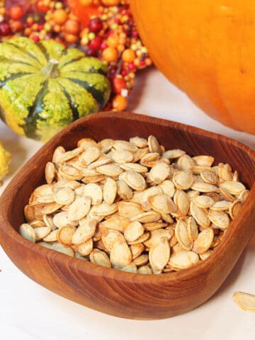 Wooden bowl filled with seeds on white table with gourds and fall leaves.